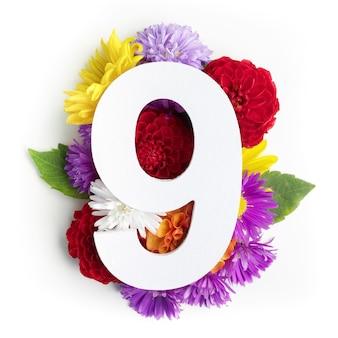 Layout com flores coloridas, folhas e número nove. postura plana. vista do topo.