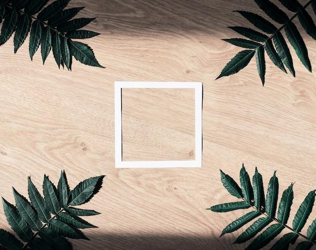 Layout com moldura de papel branco em branco e folhas verdes sobre fundo de madeira.