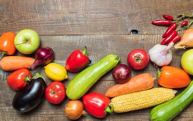 Layout com vegetais diferentes na mesa de madeira velha.