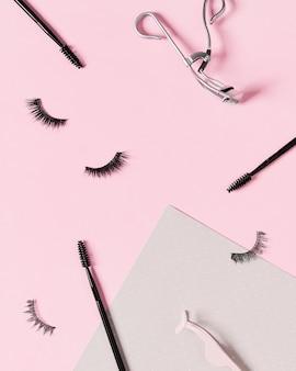 Layout criativo com acessórios de maquiagem em fundo rosa pastel