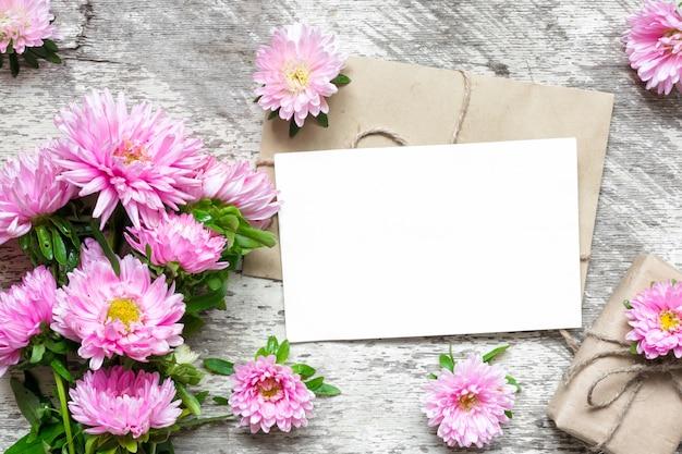 Layout criativo com cartão greeeting branco em branco, flores de áster, caixa de presente e botões de flores