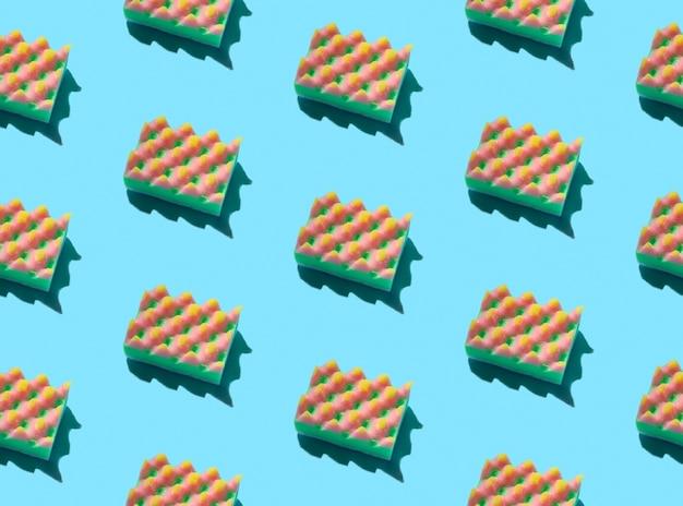 Layout criativo com esponjas para lavar louça em fundo azul. conceito de serviço de limpeza
