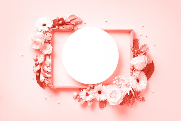 Layout criativo com flores brancas, círculo de papel para copyspace sobre fundo rosa pastel. conceito de primavera e verão na cor coral viva.