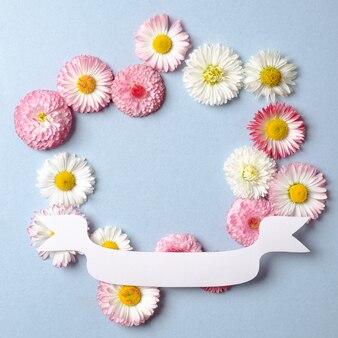 Layout criativo com flores da primavera e fita de papel festivo.