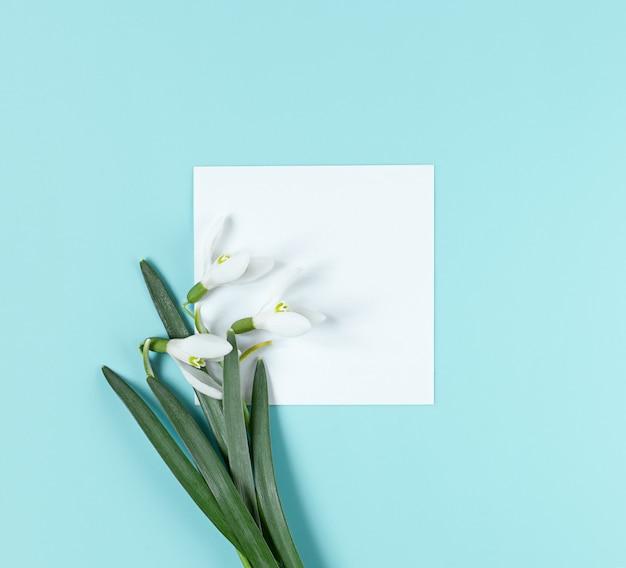Layout criativo com flores de floco de neve e papel branco para espaço de cópia em fundo azul