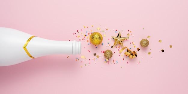 Layout criativo com garrafa de champanhe e decoração de glitter dourados.