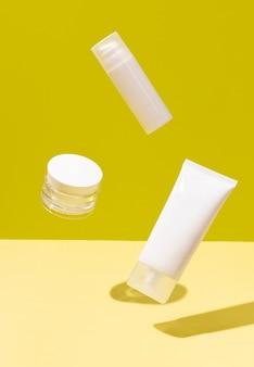 Layout criativo com levitando produtos de beleza na superfície amarela. conceito de tratamento de beleza de cuidados com o corpo. rotina de cuidados com a pele
