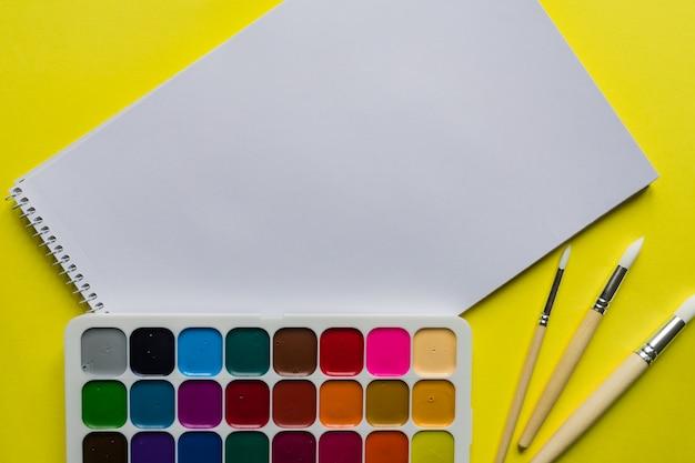 Layout criativo com paleta aquarelle, pincéis e caderno na parede amarela. copie o espaço para texto.