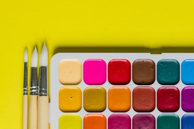 Layout criativo com paleta aquarelle, pincéis na parede amarela. vista do topo. conceito de artistas, cópia espaço para texto.