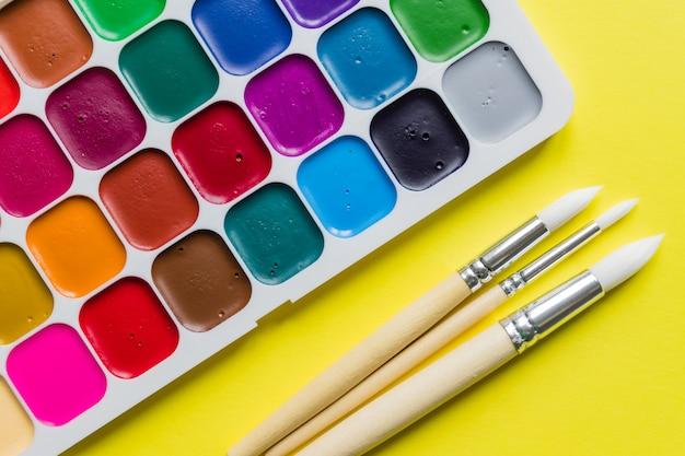 Layout criativo com paleta aquarelle, pincéis na parede amarela. vista do topo. conceito de artistas.