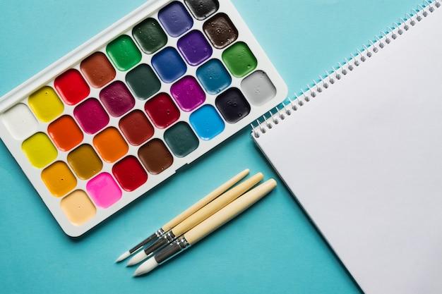 Layout criativo com paleta aquarelle, pincéis na parede azul. vista do topo. conceito de artistas.