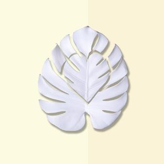 Layout criativo com recorte de folhas de monstera brancas em um fundo em forma de coração rosa pastel e amarelo