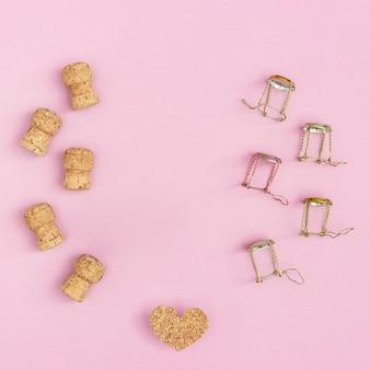 Layout criativo com rolhas de cortiça e muselets de champanhe e coração em papel rosa com espaço de cópia.