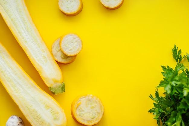 Layout criativo de abobrinha amarela sólida e fatiada em fundo amarelo