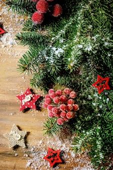 Layout criativo de ano novo de natal ou cartão com galhos de árvores de abeto, bagas vermelhas e estrelas sobre a superfície de madeira. camada plana, espaço de cópia
