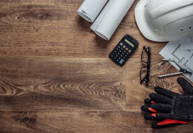 Layout criativo de arquitetos com desenhos de rolo, plano de projeto arquitetônico, ferramentas de engenharia e papelaria no chão, espaço de trabalho. vista do topo. postura plana. copie o espaço
