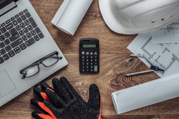 Layout criativo de arquitetos com plano de projeto arquitetônico, ferramentas de engenharia e artigos de papelaria, laptop no chão, espaço de trabalho. vista do topo. postura plana.