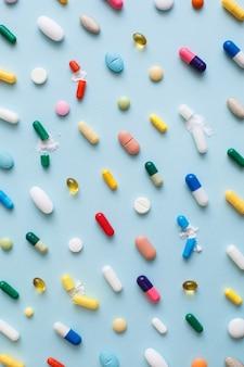 Layout criativo de comprimidos coloridos e cápsulas sobre fundo azul.