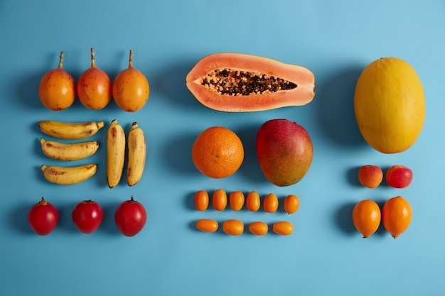 Layout criativo de suculentas frutas tropicais sobre fundo azul. bananas maduras, fortunella vermelha, laranjas, pêssegos, metade de mamão, cumquat. frutas exóticas para uma alimentação saudável. alimentação limpa, vitaminas