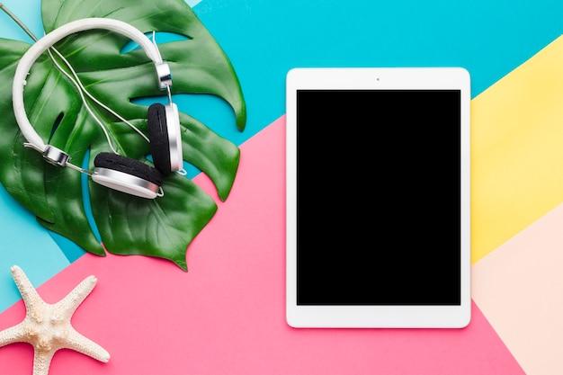 Layout criativo de tablet e fones de ouvido