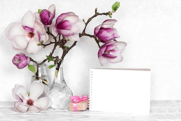 Layout criativo feito com flores de magnólia rosa, cartão vazio e caixa de presente em fundo branco de madeira