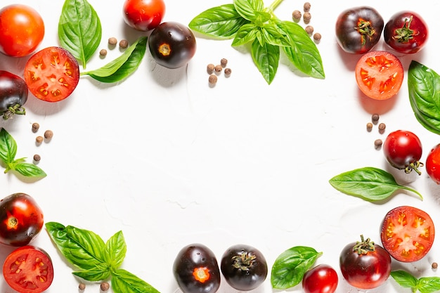 Layout criativo feito com tomates maduros, manjericão aromático fresco e pimenta da jamaica em fundo de pedra branca.