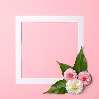 Layout criativo feito de borda de quadro de papel e flores de primavera concurso em fundo rosa pastel.