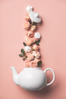 Layout criativo feito de bule de chá whte com rosas laranja e merengues em rosa