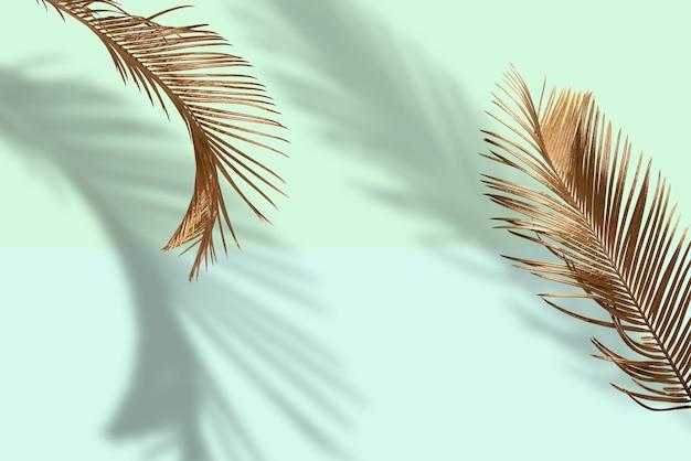 Layout criativo feito de folhas de palmeira douradas sobre fundo verde pastel. idéia de novidade mínima para o verão