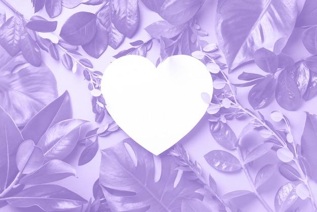 Layout criativo feito de folhas tropicais, papel em forma de coração na cor violeta na moda.