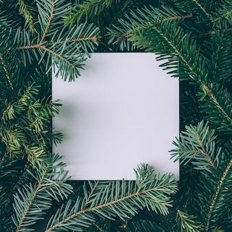Layout criativo feito de galhos de árvores de natal com nota de cartão de papel. postura plana. conceito de ano novo da natureza.