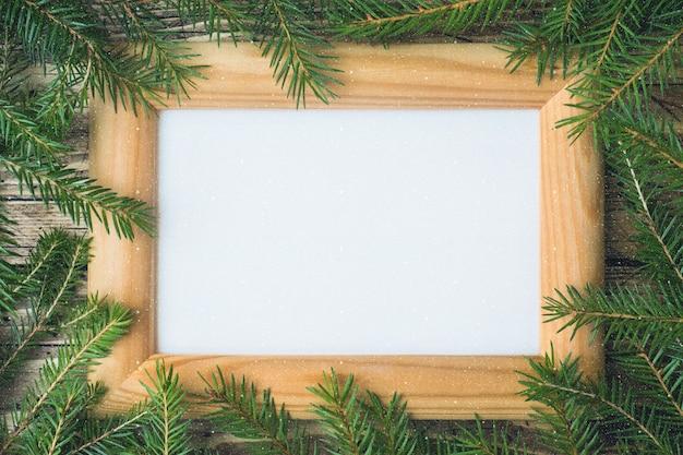Layout criativo feito de galhos de árvores de natal com nota de cartão de papel.