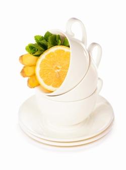 Layout criativo feito de xícara de chá de hortelã, limão e gengibre em um fundo branco. vista do topo.