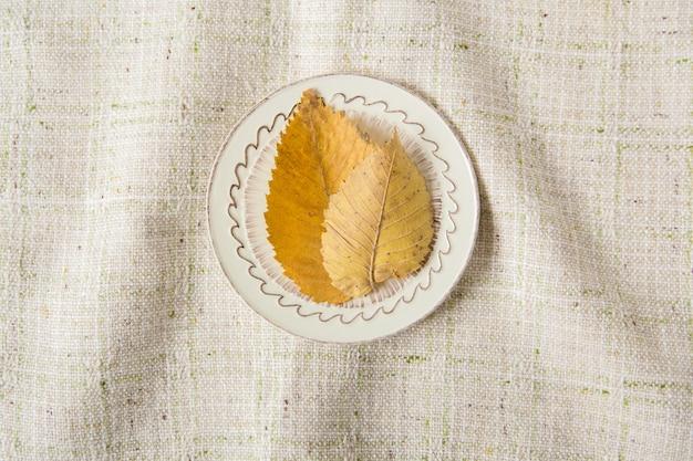Layout criativo. folhas de outono amarelas na placa. espaço para texto. estilo minimalista. fundo de toalha de mesa