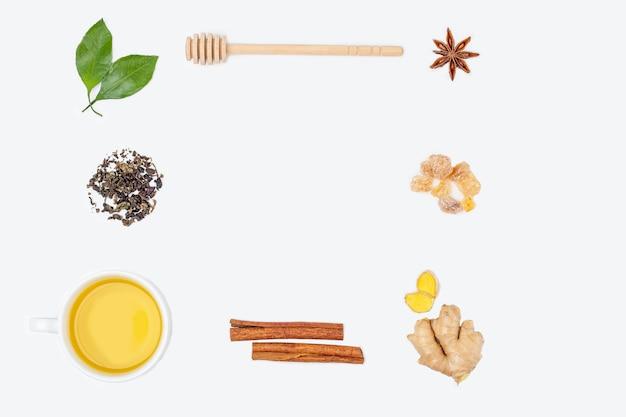 Layout da xícara de chá oolong com folhas frescas, heap chá verde seco, açúcar doce e raiz de gengibre no fundo branco, copie o espaço para texto. ervas orgânicas, chá asiático verde para a cerimônia do chá. configuração plana