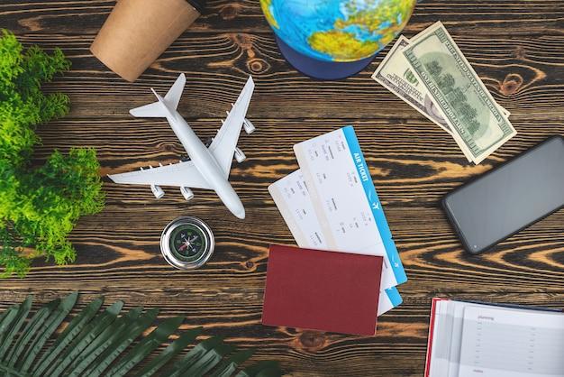 Layout de acessórios de viagem de avião em um fundo de madeira