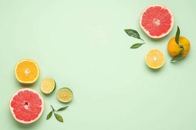 Layout de alimentos bem organizado de frutas e folhas em fundo verde pastel
