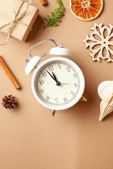 Layout de ano novo com presente de despertador tempera o conceito de véspera de ano novo, um presente com sua própria mão ...