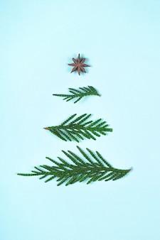 Layout de árvore de natal de galhos verdes sobre fundo azul.