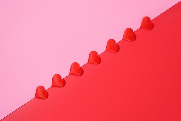 Layout de cartão de dia dos namorados com corações vermelhos em fundo rosa e vermelho, para texto local. fundo de casamento festivo.