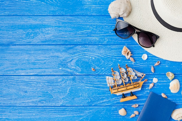 Layout de conchas do mar perto de navio de brinquedo e óculos de sol com chapéu