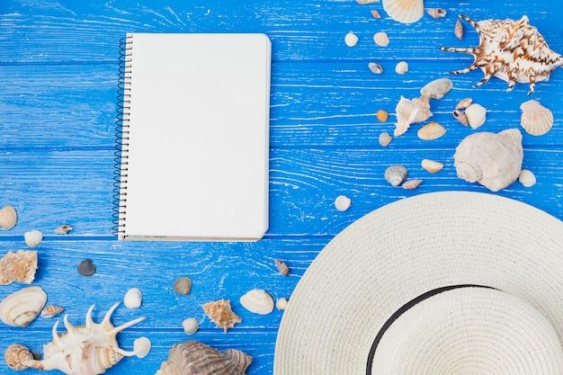 Layout de conchas e chapéu perto de bloco de notas
