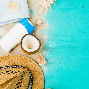 Layout de conchas perto de chapéu e coco entre areia