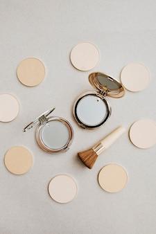 Layout de cosméticos. refil de pó em diferentes tons de pele e base tonal pressionada ao lado do pincel de maquiagem