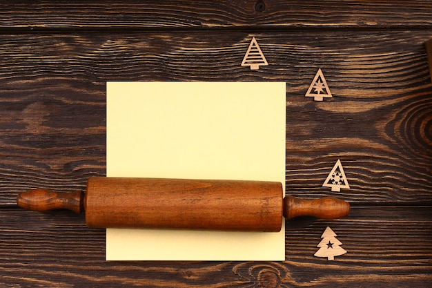 Layout de culinária de natal em um fundo de madeira. rolo de rolo de madeira com elementos de natal e uma folha para registar o menu festivo da mesa. vista superior, estilo plano.