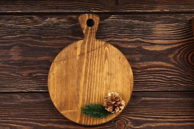 Layout de culinária de natal em um fundo de madeira. tábua de corte de madeira com artigos de natal para o menu da mesa do feriado. vista superior, estilo plano.