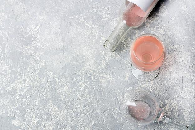 Layout de degustação de vinho rosa. abriu a garrafa e dois copos com vinho rosé, sobre um fundo cinza. conceito de embriaguez.