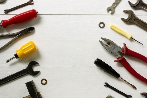 Layout de ferramentas de reparo e construção em um fundo branco de madeira