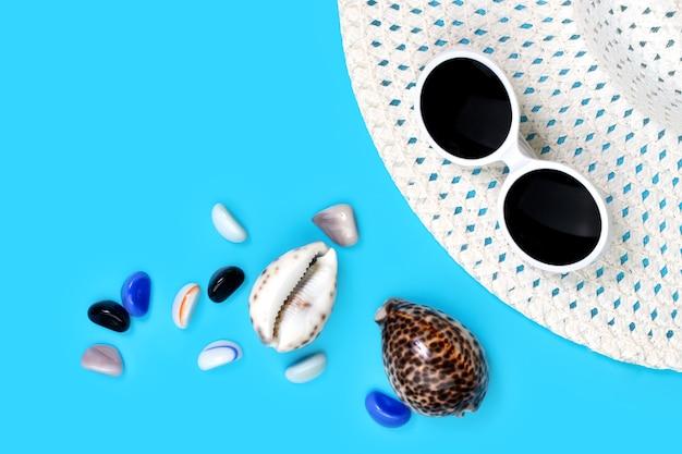 Layout de fundo azul chapéu de praia feminino, óculos de sol e conchas