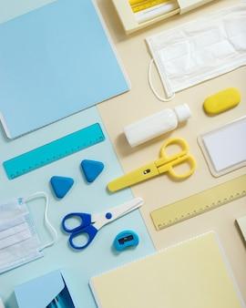 Layout de material escolar, cadernos, canetas, lápis, máscara médica e desinfetante para as mãos